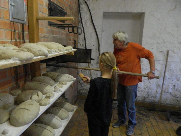 Günther Schmidt hat über viele Jahre Brot gebacken. Hier zeigt er es Mellnauer Kindern, wie es geht, Foto A. Völk Aug. 2019